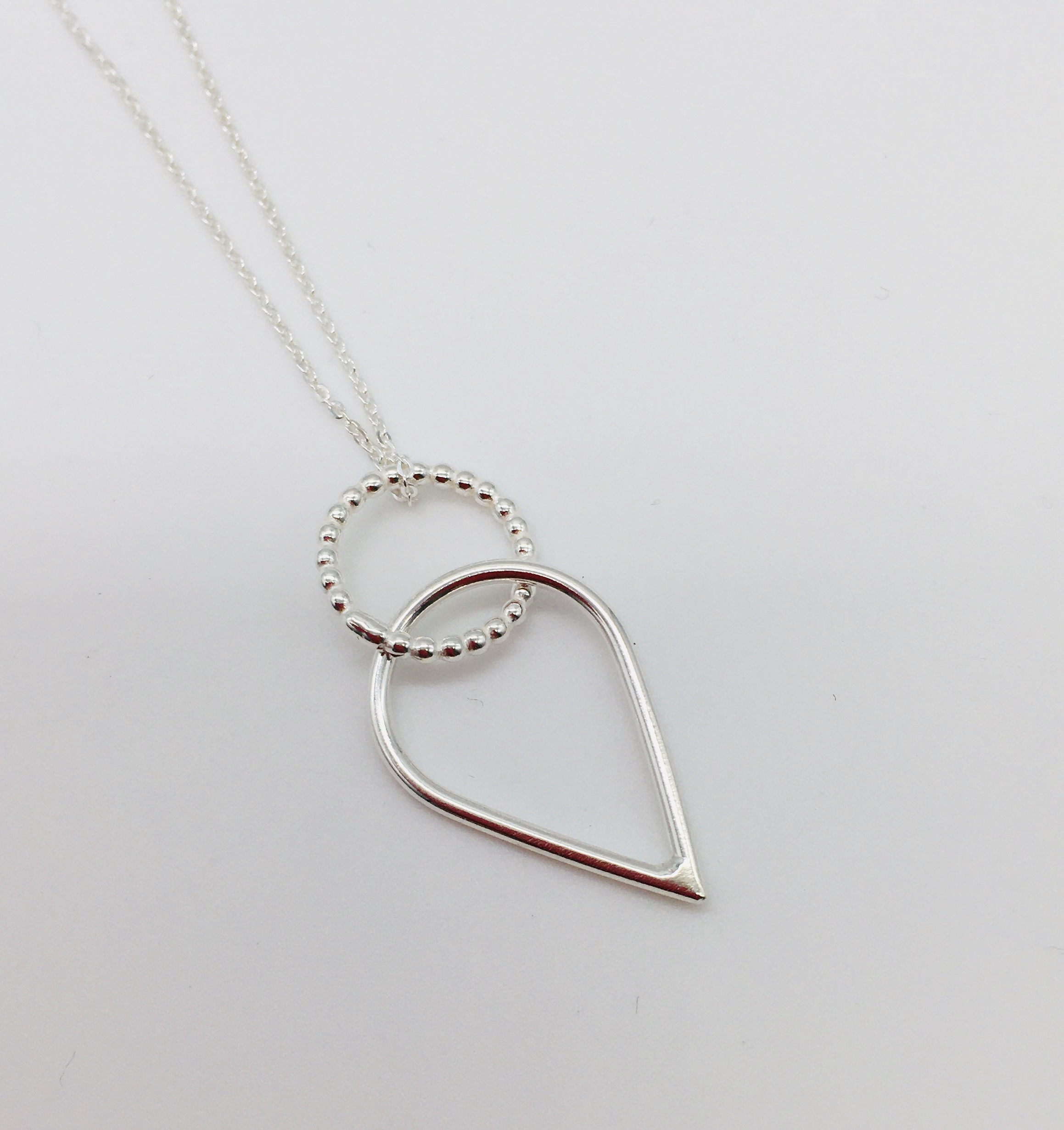 Dotty Circle and Teardrop Pendant in silver, handmade in Devon by silversmith Claire Lowe.